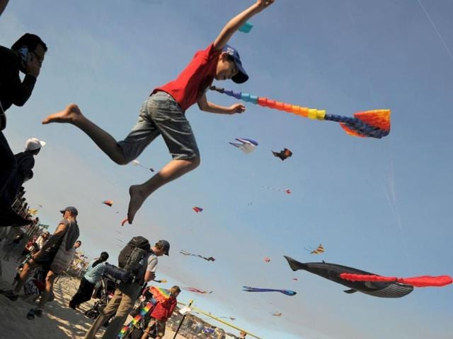 A-boy-jumps-from-the-walkway-at-the-Sydney-s-Bondi-Beach-while-giant-kites-fly-in-the-background-during-the-annual-Festival-of-the-Winds-AFP-photo-Romeo-Gacad