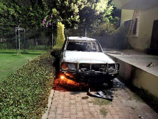 A burnt out vehicle sits smoldering in flames after it was set on fire inside the US consulate compound in Benghazi. AFP