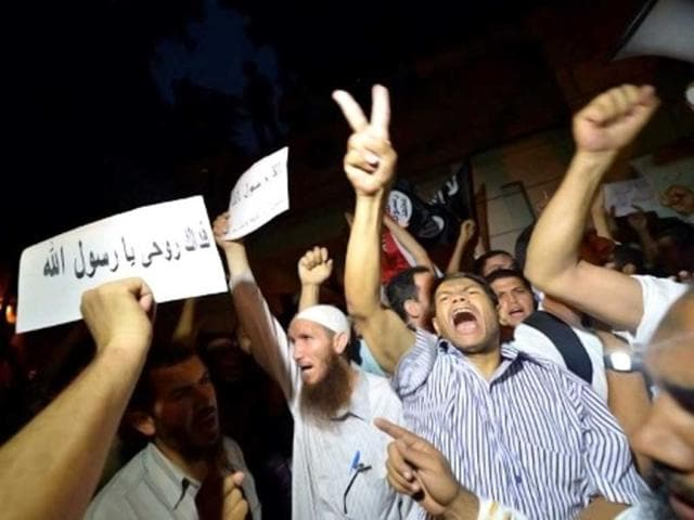 "An Egyptian protester hold a sign that reads in Arabic ""I sacrifice my soul for God"