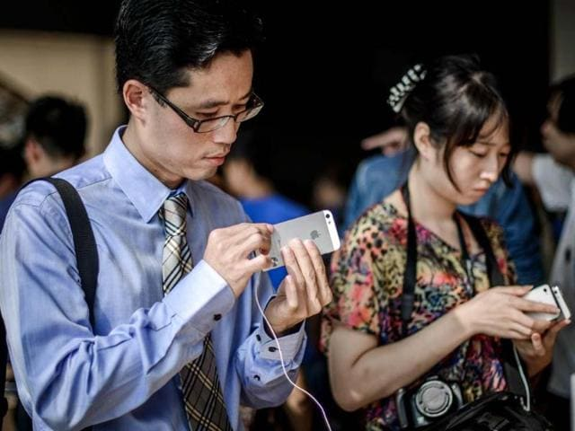 A-man-checks-an-iPhone-5-at-the-Hong-Kong-Apple-store-AFP-Philippe-Lopez