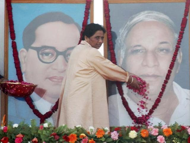 Bahujan Samaj Party supremo Mayawati offers flowers to a photograph of party founder Kanshiram during a rally commemorating his sixth death anniversary in Lucknow. AFP