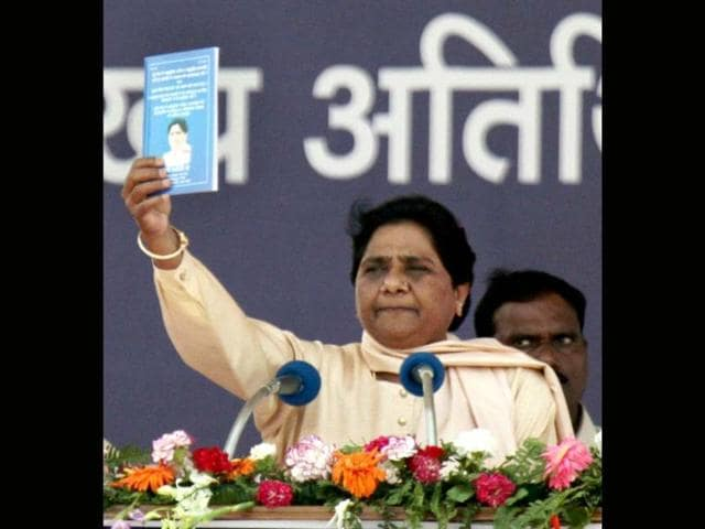 BSP supremo Mayawati shows a book while addressing a party rally on the occasion of party founder Kanshiram's sixth death anniversary in Lucknow. PTI/Nand Kumar