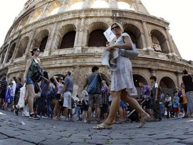 Tourists-walk-in-front-of-Rome-s-ancient-Colosseum-Credit-Reuters-Alessandro-Bianchi