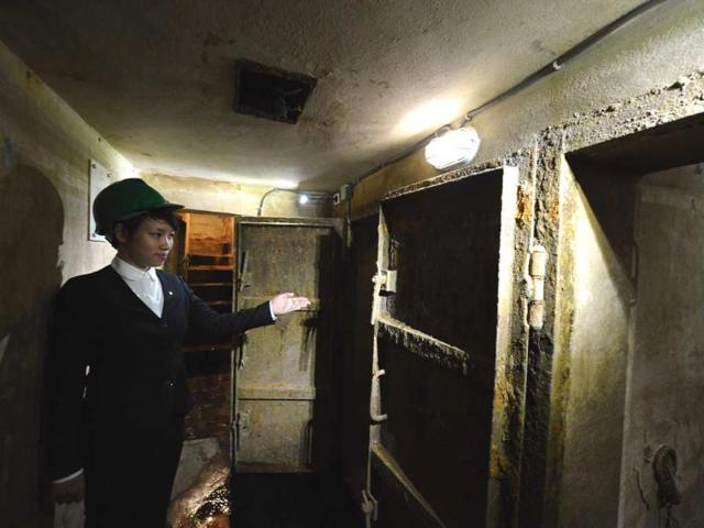 This-picture-taken-on-October-2-2012-shows-a-Metropole-hotel-employee-guiding-a-visitor-to-its-war-time-bomb-shelter-in-Hanoi-Photo-AFP-Hoang-Dihn-Nam