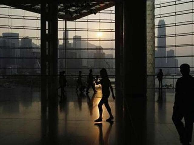 People-walk-inside-the-Hong-Kong-Convention-and-Exhibition-Centre-as-the-sun-sets-behind-the-Hong-Kong-skyline-Credit-Reuters-Bobby-Yip