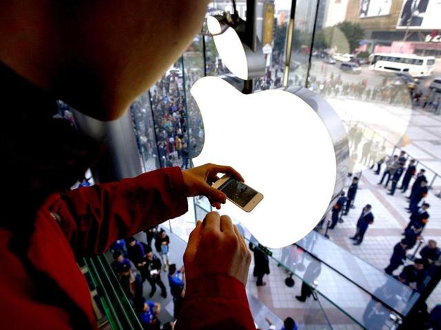 A-man-takes-a-photograph-using-his-iPhone-of-members-of-the-public-entering-a-new-Apple-store-during-the-official-opening-in-Beijing-Reuters-David-Gray