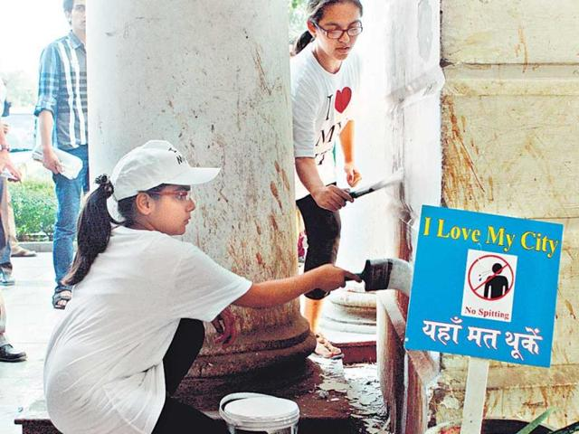 Volunteers-painting-a-stained-pillar-in-Connaught-Place-New-Delhi-Sushil-Kumar-HT