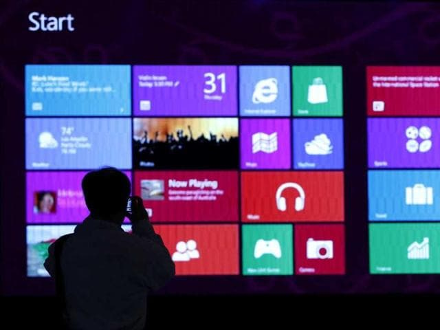 A-man-takes-pictures-of-a-monitor-during-an-event-promoting-the-debut-of-Microsoft-Corp-s-Windows-8-operating-system-at-the-Akihabara-electronic-shops-district-in-Tokyo-Reuters-Toru-Hanai