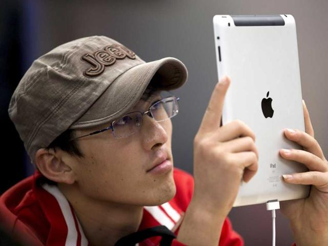 A-customer-tries-out-an-iPad-at-an-Apple-Store-in-Beijing-Apple-the-world-s-most-valued-company-has-announced-new-top-executives-to-lead-it-AP-Photo-Andy-Wong