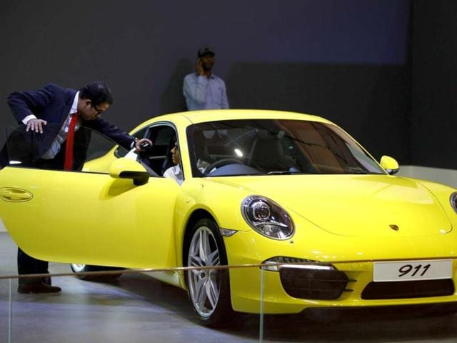 A sales executive briefs a visitor about a Porsche 911 Carrera displayed during the Autocar Performance Show in Mumbai. AP Photo