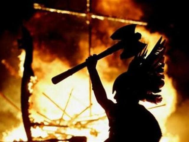 A-Junior-Up-Helly-Aa-Viking-lifts-his-axe-upwards-as-a-longboat-burns-behind-him-during-the-Up-Helly-Aa-festival-in-Lerwick-the-Shetland-Islands-northern-Scotland-Credit-Reuters-David-Moir