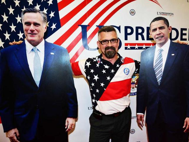 A-man-poses-between-two-cardboard-portraits-of-US-President-Barack-Obama-and-Republican-Presidential-candidate-Mitt-Romney-during-the-US-election-night-party-in-Milan-AFP-photo