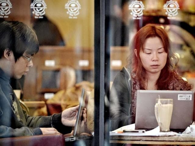 People-surf-the-internet-on-a-laptop-using-the-wi-fi-connection-of-a-cafe-in-Shanghai-Photo-AFP-Philippe-Lopez