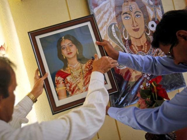 Andanappa-Yalagi-L-father-of-Savita-Halappanavar-is-helped-by-a-friend-as-he-hangs-her-portrait-at-their-house-in-Belgaum-Reuters-Danish-Siddiqui