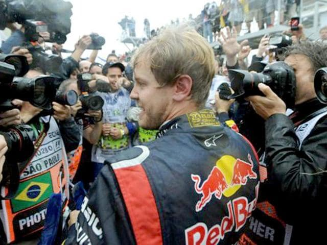 Sebastian-Vettel-is-surrounded-by-photographers-as-he-celebrates-his-F-1-World-Championship-after-arriving-6th-in-the-Brazil-F-1-GP-at-the-Interlagos-racetrack-in-Sao-Paulo-Brazil--AFP-PHOTO-ANTONIO-SCORZA