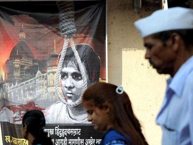 Pedestrians-walk-past-a-poster-depicting-the-hanging-of-Pakistani-born-Mohammed-Ajmal-Kasab-the-sole-surviving-gunman-from-the-2008-Mumbai-attacks-outside-a-railway-station-in-Mumbai-AFP-Indranil-Mukherjee