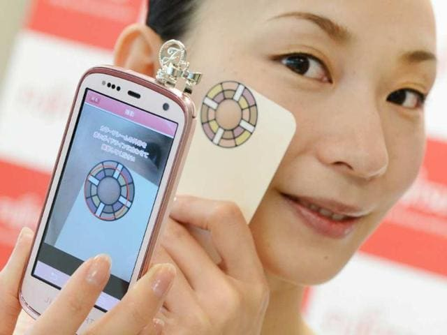 A-model-demonstrates-how-to-take-pictures-of-her-face-with-a-smart-phone-to-chech-her-skin-condition-through-a-cloud-computer-system-produced-by-Japan-s-computer-maker-Fujitsu-during-a-press-conference-in-Tokyo-Photo-AFP-Toru-Yamanaka