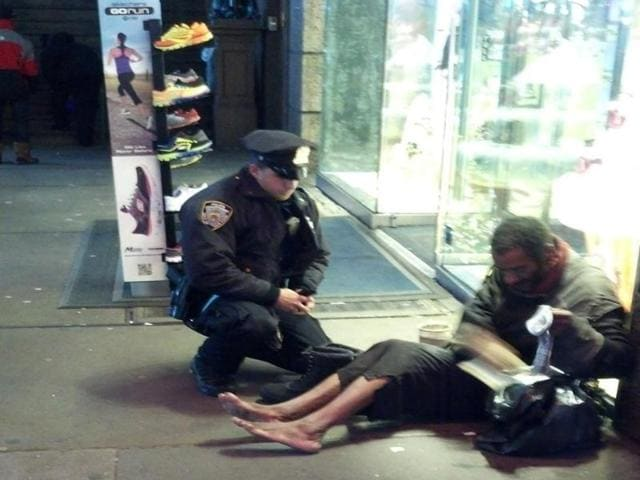 New-York-City-Police-Officer-Larry-DePrimo-presenting-a-barefoot-homeless-man-in-New-York-s-Time-Square-with-boots-AP
