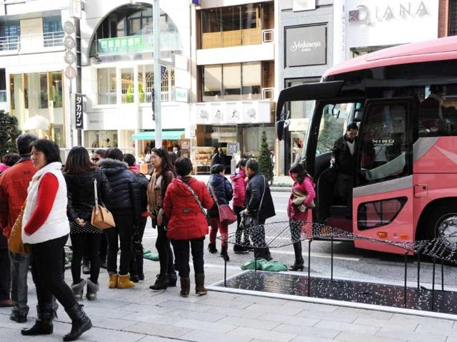 This-picture-taken-on-December-2-2012-shows-Chinese-tourists-disembarking-from-a-bus-at-the-Ginza-shopping-district-in-Tokyo-Photo-AFP-Toshifumi-Kitamura