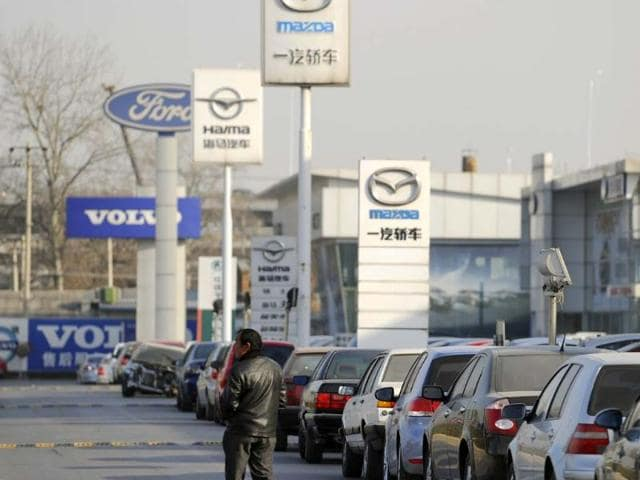 A-man-walk-past-the-various-trademarks-of-the-car-makers-at-a-car-market-in-Beijing-Photo-AFP-LIU-Jin