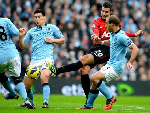 Manchester-United-s-Dutch-striker-Robin-Van-Persie-shoots-between-Manchester-City-s-Argentinian-defender-Pablo-Zabaletaand-English-midfielder-Gareth-Barry-during-the-EPL-football-match-between-Manchester-City-and-Manchester-United-at-The-Etihad-stadium-in-Manchester-AFP-Photo