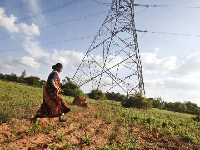 In-this-Dec-5-2012-photo-Gangarangamma-65-walks-through-the-land-she-and-her-husband-farmed-for-decades-which-the-records-show-is-registered-to-the-government-a-sign-the-land-remained-in-dispute-in-village-Karadigere-Kaval-85-kilometers-53-miles-from-Bangalore-India-For-years-Karnataka-s-land-records-were-a-quagmire-of-disputed-forged-documents-maintained-by-thousands-of-tyrannical-bureaucrats-who-demanded-bribes-to-do-their-jobs-Photo-AP-Aijaz-Rahi