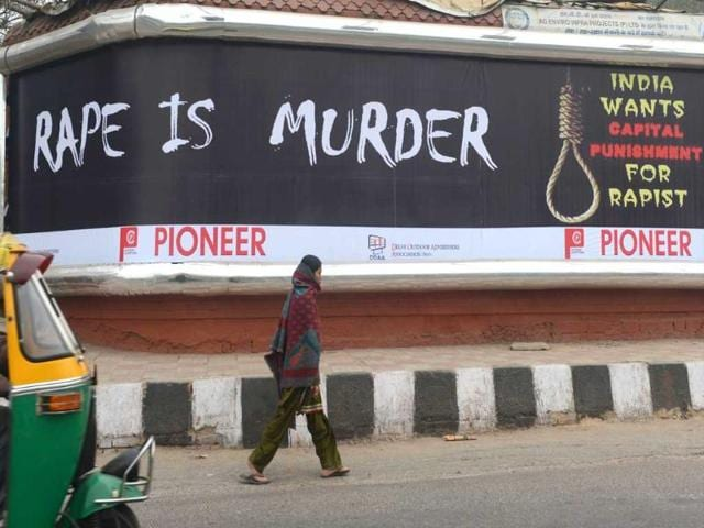 A-woman-walks-past-a-billboard-calling-for-capital-punishment-against-rape-in-New-Delhi-AFP-Raveendran