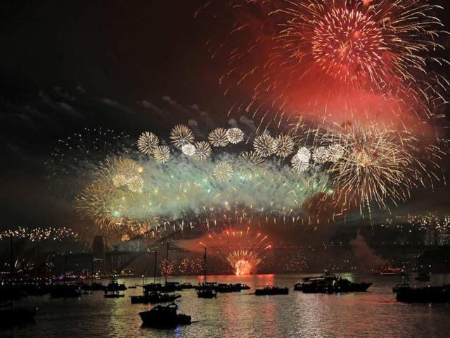 Spectator-boats-in-Sydney-Harbour-look-on-as-New-Year-s-Eve-fireworks-erupt-over-the-Sydney-Harbour-Bridge-on-January-1-2013-Photo-AFP-Greg-Wood