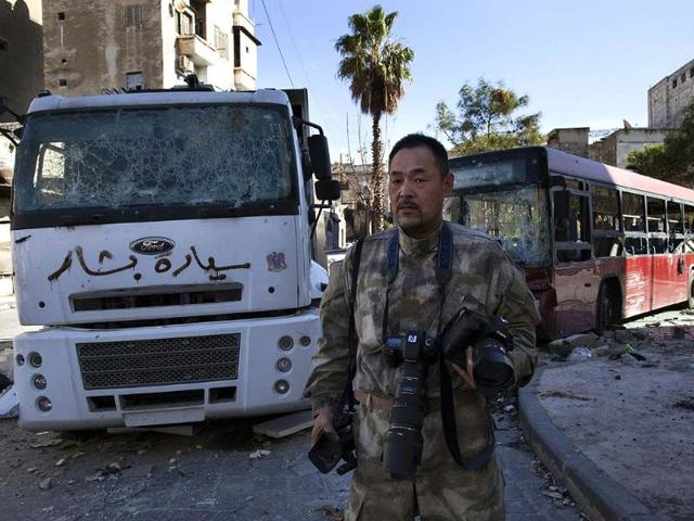 Japanese-trucker-Toshifumi-Fujimoto-holds-his-cameras-in-front-of-damaged-buses-in-Aleppo-s-old-city-on-December-27-2012-Photo-AFP-STR