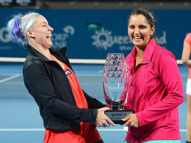 Sania-Mirza-and-her-partner-Bethanie-Mattek-Sands-of-the-US-hold-the-trophy-after-defeating-Anna-Lena-Groenefeld-of-Germany-and-Kveta-Peschke-of-the-Czech-Republic-in-the-women-s-doubles-final-at-the-Brisbane-International-tennis-tournament-AFP-William-West