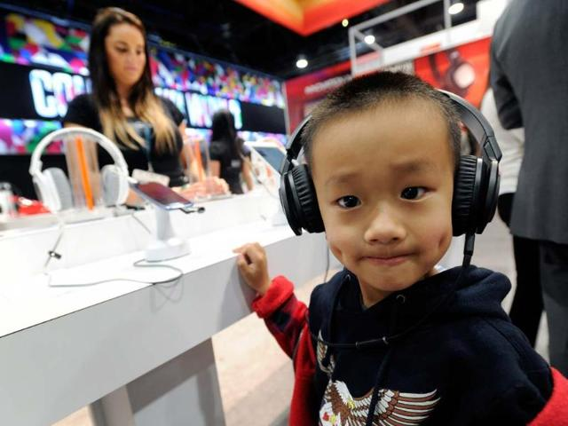 A-young-attendee-listens-to-music-on-a-pair-of-JBL-J88i-headphones-at-the-Harman-Kardon-booth-at-the-2013-International-CES-at-the-Las-Vegas-Convention-Center-on-January-9-2013-in-Las-Vegas-Nevada-CES-the-world-s-largest-annual-consumer-technology-trade-show-runs-through-January-11-and-is-expected-to-feature-3-100-exhibitors-showing-off-their-latest-products-and-services-to-about-150-000-attendees-Photo-David-Becker-Getty-Images-AFP