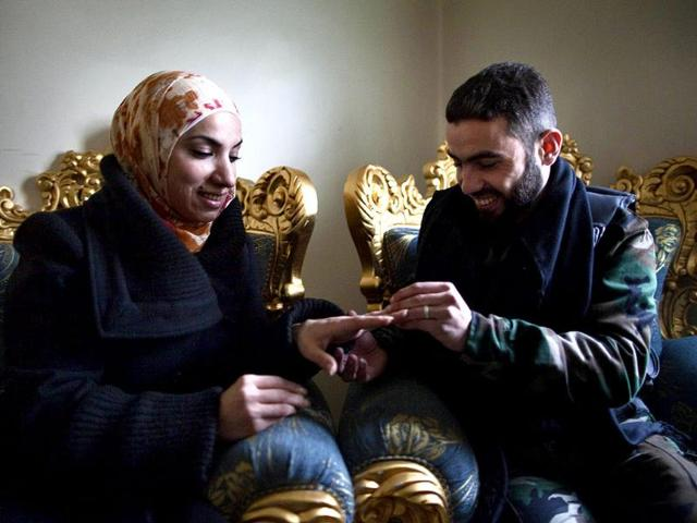 Yusef-puts-a-wedding-ring-on-his-fiancee-Ghada-s-finger-in-the-Sukkari-district-of-Aleppo-in-northern-Syria-AFP-JM-Lopez