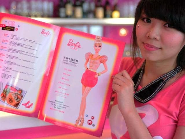 A-waitress-holds-up-a-menu-during-the-opening-ceremony-of-a-Barbie-themed-restaurant-in-Taipei-on-January-30-2013-With-hot-pink-sofas-high-heels-shaped-tables-and-chairs-decorated-with-tutus-the-first-Barbie-themed-restaurant-opened-in-Taiwan-on-January-30-catering-to-fans-of-the-iconic-doll-Photo-AFP-Sam-Yeh
