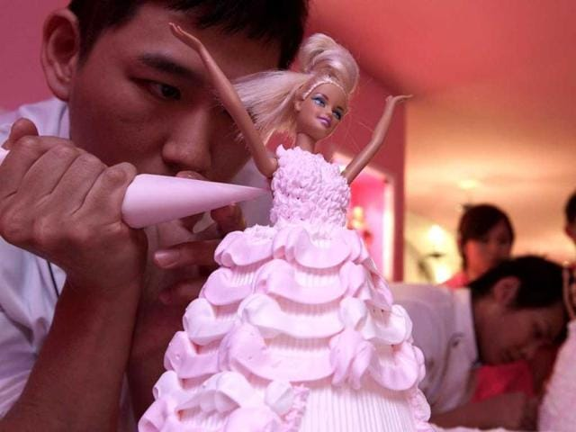 A-man-decorates-a-Barbie-doll-cake-during-a-media-preview-of-the-Barbie-Cafe-in-Taipei-Reuters