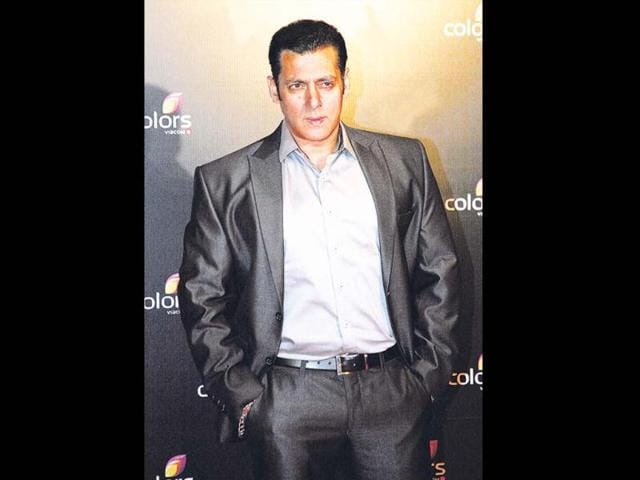 Mandira-Bedia-R-looks-on-as-Bollywood-film-actor-Salman-Khan-takes-off-his-jacket-during-the-launch-of-his-Being-Human-flagship-clothing-store-in-Mumbai-on-January-17-2013-Khan-announced-the-pan-India-launch-of-his-flagship-retail-store-for-Being-Human-fashion-apparel-after-having-already-launched-in-Paris-Belgium-Spain-and-Dubai-AFP-PHOTO