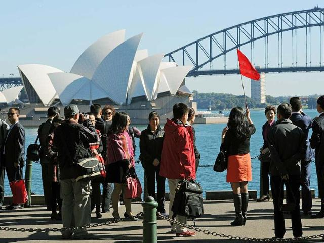 A-group-of-Asian-tourists-arrive-to-have-their-photograph-taken-in-front-of-the-Sydney-Opera-House-and-Harbour-Bridge-Photo-AFP-Greg-Wood