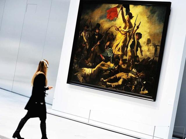 A-file-picture-at-the-Louvre-Lens-Museum-in-the-French-northern-city-of-Lens-shows-a-visitor-passing-by-La-liberte-guidant-le-peuple-d-Eugene-Delacroix-A-woman-vandalised-the-painting-by-writing-on-it-with-a-black-permanent-marker-AFP-Philippe-Huguen