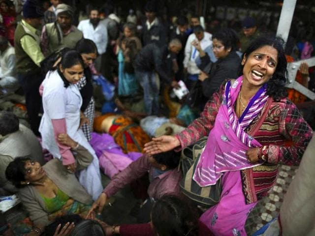 A woman weeps as she and other family members mourn next to the body of a relative who was killed in a stampede on a railway platform at the main railway station in Allahabad (AP Photo)