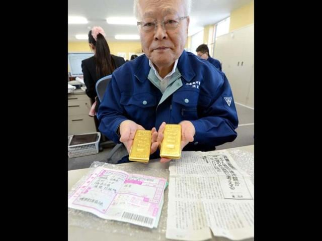 Kunio-Sunow-president-of-the-Ishinomaki-Fish-Market-shows-off-two-slabs-of-gold-each-weighing-one-kilogram-2-2-pounds-as-well-as-the-parcel-s-invoice-bottom-L-and-an-enclosed-magazine-article-bottom-R-at-his-office-in-Ishinomaki-Miyagi-prefecture-AFP