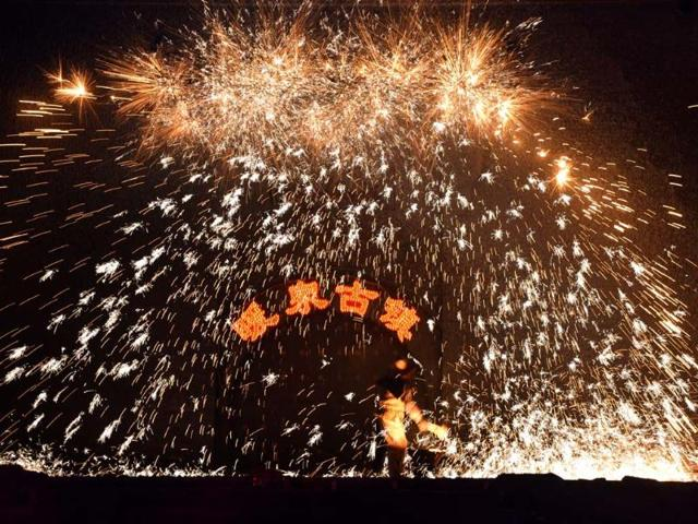 A-Chinese-blacksmith-throws-molten-metal-against-a-cold-stone-wall-to-create-sparks-during-the-Lantern-Festival-which-traditionally-marks-the-end-of-the-Lunar-New-Year-celebrations-in-Nuanquan-Hebei-province-on-February-24-2013--Photo-AFP-Mark-Ralston