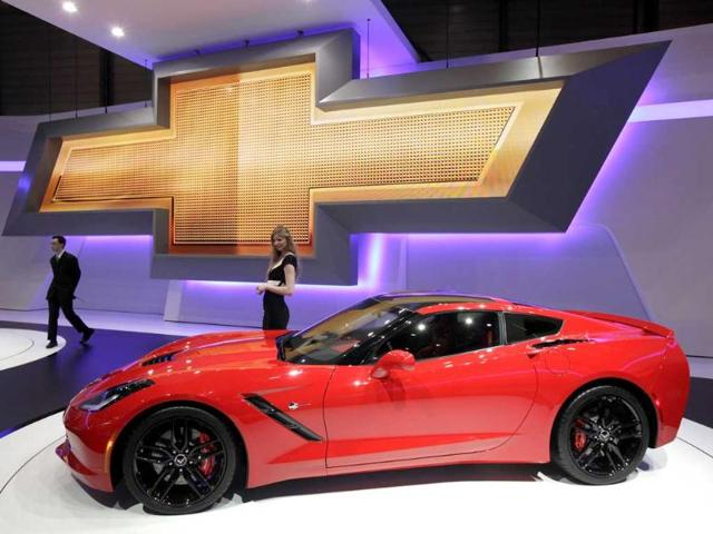 A model stands next to a Corvette car on the Chevrolet booth during the second media day of the 83rd Geneva Car Show at the Palexpo Arena in Geneva. (Reuters)