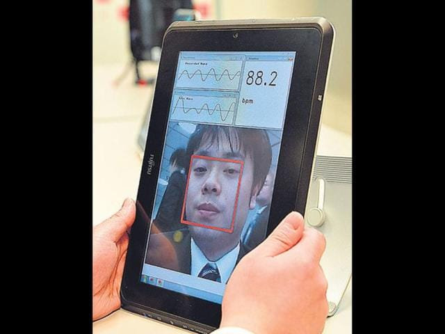 A-Fujitsu-engineer-shows-a-the-real-time-pulse-monitor-system-with-facial-imaging-technology-in-Tokyo-AFP-photo