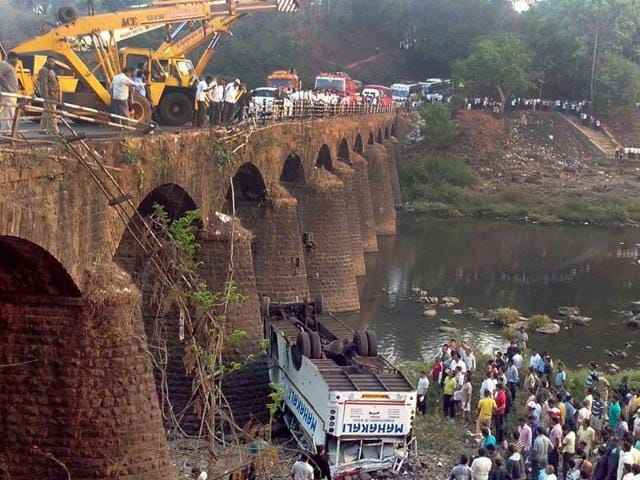 Rescue-officials-and-bystanders-gather-around-the-wreckage-of-a-bus-after-it-fell-from-a-bridge-at-Khed-some-350-kilometers-220-miles-south-of-Mumbai-AFP-Str