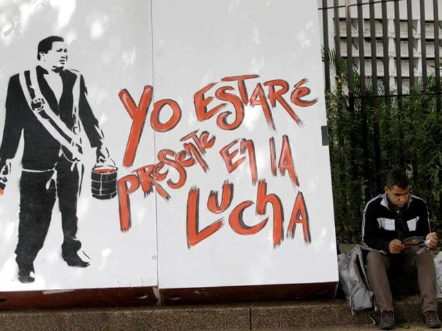 A-man-reads-a-book-as-he-sits-next-to-a-stencil-mural-depicting-Venezuela-s-former-President-Hugo-Chavez-holding-a-bucket-of-red-paint-and-a-brush-that-reads-in-Spanish-I-ll-be-present-in-the-fight-during-the-annual-book-fair-in-Caracas-Venezuela-AP