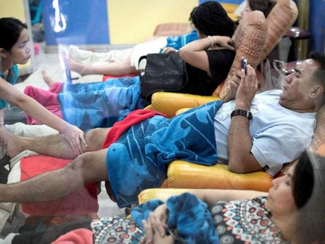 A--man-gets-a-foot-massage-while-using-his-smartphone-at-a-shopping-mall-in-Bangkok-A-recent-Facebook-sponsored-study-shows-smartphone-owners-are-often-connected-all-day-People-can-be-found-glued-to-their-smartphones-even-while-crossing-the-street-creating-a-disconnect-with-their-immediate-surroundings-AFP-Photo