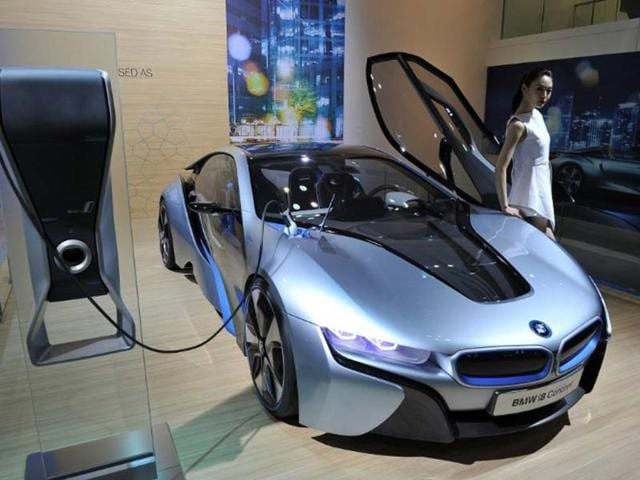This-picture-taken-on-March-28-2013-shows-a-South-Korean-model-posing-with-BMW-i8-Concept-during-a-press-preview-of-the-Seoul-Motor-Show-in-Goyang-north-of-Seoul-Gas-guzzling-SUVs-eco-friendly-electric-cars-and-the-odd-brave-attempt-to-marry-the-selling-points-of-both-are-taking-centre-stage-at-the-biennial-Seoul-Motor-Show-Photo-AFP