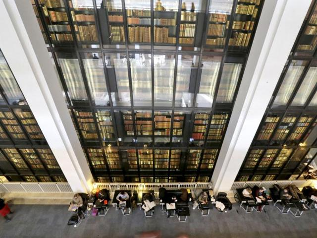 People-work-on-their-computers-as-old-books-kept-at-the-British-Library-are-displayed-in-London-AP
