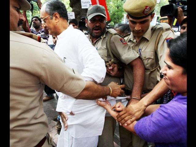 Policemen push away a SFI activist holding the kurta (shirt) of West Bengal finance minister Amit Mitra as he arrives to meet Deputy Chairman of Planning Commission Montek Singh Ahluwalia in New Delhi. SFI activists were protesting over the death of student leader Sudipto Gupta. PTI Photo
