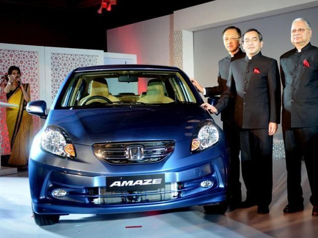 President-and-CEO-of-Honda-Cars-India-Limited-Hironori-Kanayama-C-Managing-Officer-Honda-Motor-Company-Yoshiyuki-Matsumoto-R-and-senior-Vice-President-of-Honda-Raman-Kumar-Sharma-L-pose-during-the-launch-of-Honda-s-new-Amaze-diesel-engine-car-in-New-Delhi-AFP