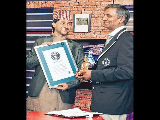 TV-presenter-Rabi-Lamichhane-left-is-presented-with-a-certificate-by-a-Guinness-World-Records-official-AFP-photo